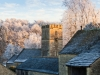 The sun setting on St Andrews church in the hoar frost covered Cotswold village of Coln Rogers, Gloucestershire
