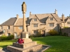 Evening sunlight falling on the war memorial and cottages on the village green in the Cotswold village of Guiting Power, Gloucestershire