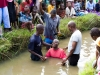 Adult Christian baptism in a shallow river in the village of Nyombe, Malawi, Africa