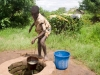 Boy drawing water from a well  in the village of Mombala (Mambala), Malawi, Africa