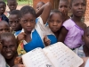 School children and a reading primer for the Chichewa language in the village of Chagamba, Malawi, Africa