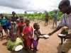 Serving phala (maize porridge) to hungry children as part of the Joseph Project feeding programme in the village of Buli, Malawi, Africa