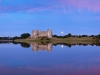 The moon rising behind Carew Castle beside the Carew River at Carew, Pembrokeshire, Wales